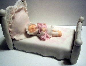 Sleeping fondant baby in bed